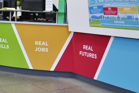A close up of the branded reception desk at Heart of Worcestershire College All Saints' Building
