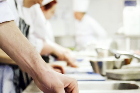 A close up of a group of student chefs working in a hospitality kitchen