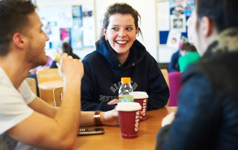 Female student laughing and sat drinking coffee with two male students.