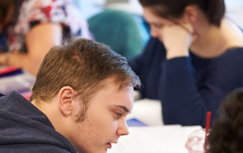 Male student completing work at a desk with other students in the background.