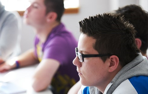Side profile of male student listening to lecturer in classroom.