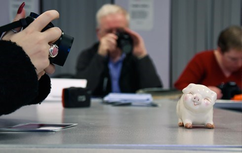 Image of white piggy bank on desk with student holding a camera and taking a photo.