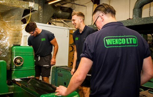 3 males working on green machinery and wearing 'Wexco Ltd' tshirts.