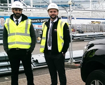 Two men in high visibility jackets stood next to electric car
