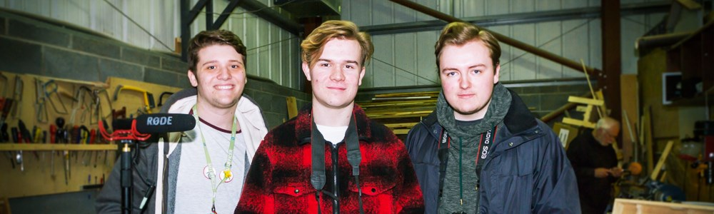 Three male students smiling with camera equipment in a construction warehouse
