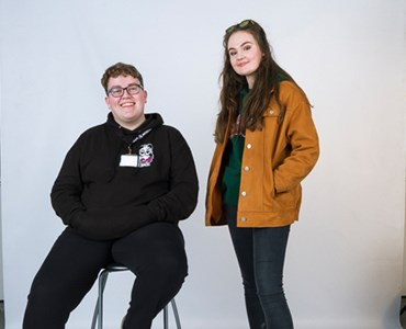 Male and female student smiling in a photography studio