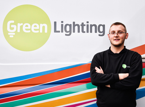 Male smiling with his arms folded and stood in front of a company logo that reads: Green Lighting