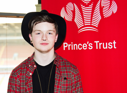 Male student stood smiling in front of red vertical banner that reads: Prince's Trust
