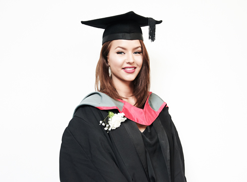 Graduation photo of smiling female wearing a cap and gown in front of a white backdrop