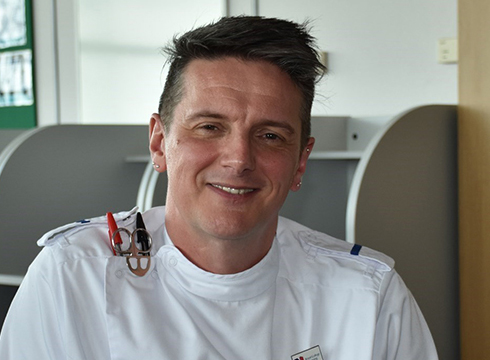 Close up image of male wearing a white medical uniform and smiling