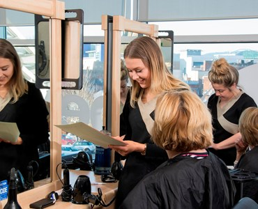 Two hair salon stations with women sat wearing black hairdressing capes; two female students smiling and attending to the clients.