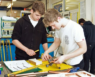 Two male students working together at a large desk with measuring equipment.
