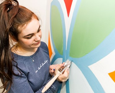 Female student painting wall.