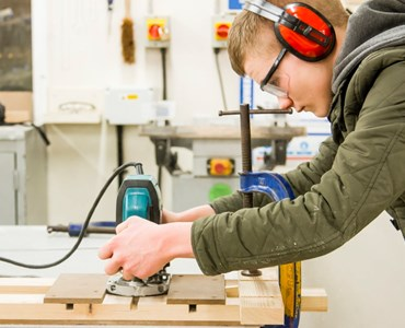 Male student with protective goggles and ear protectors using sander.