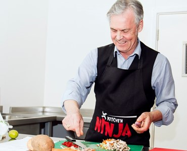 Grey haired man wearing black apron and smiling while preparing food on a green chopping board.
