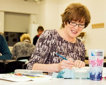 Mature female student smiling while sat at a desk painting with water colours.