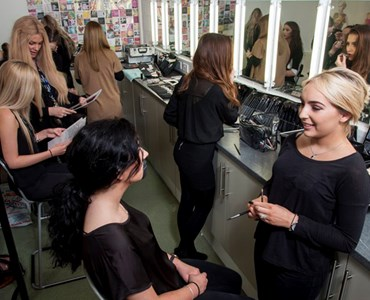 Group of female clients sat at makeup stations with female students gathered round and doing makeup and hair