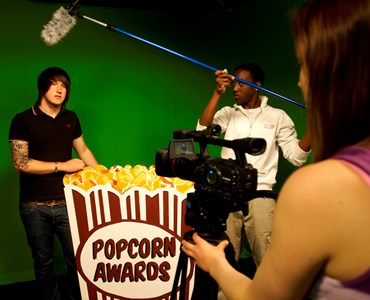 3 students in a green screen room, one student is behind the camera, one holding a microphone and the other student is stood behind a large popcorn cardboard cut