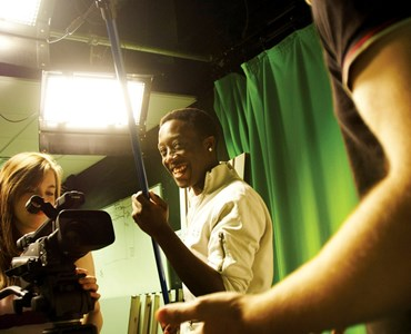 3 students in a green screen studio, one student is stood behind a large recording camera and one is holding a recording microphone