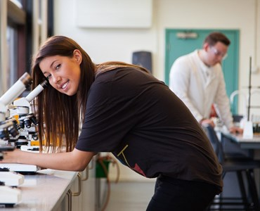 A female student leaning over a microscope smiling at the camera. A male student is in the background wearing protective goggles leaning over a desk