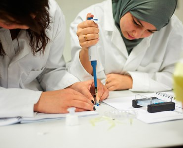 2 female students in science laboratory coats sat at a desk together concentrating on a science experiment
