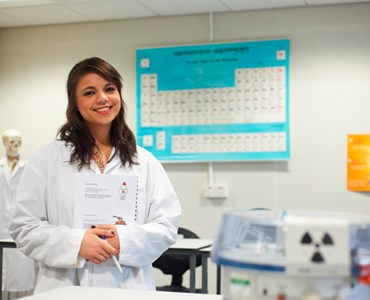 A female student in a laboratory coat holding a workbook stood in a science laboratory smiling at the camera