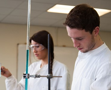 A female and male student in a science laboratory in protective lab coats,  the female student is wearing protective goggles and is holding a test tube with blue liquid