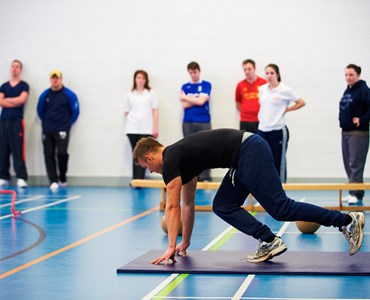 A group of students stood in an indoor sports hall watching a male student on a mat in a starting running position