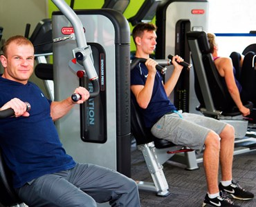 2 male students sat inside a gym using weight machines