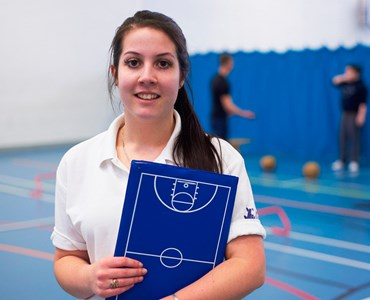 A female student in a white polo shirt holding a blue folder stood in an indoor sports hall smiling at the camera