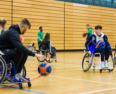 A group of students playing indoor wheelchair basketball with 2 referees in a green t-shirt watching
