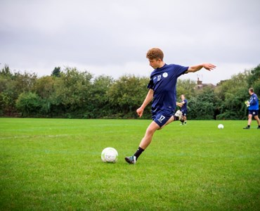 Male student in a blue football kit about to kick a football