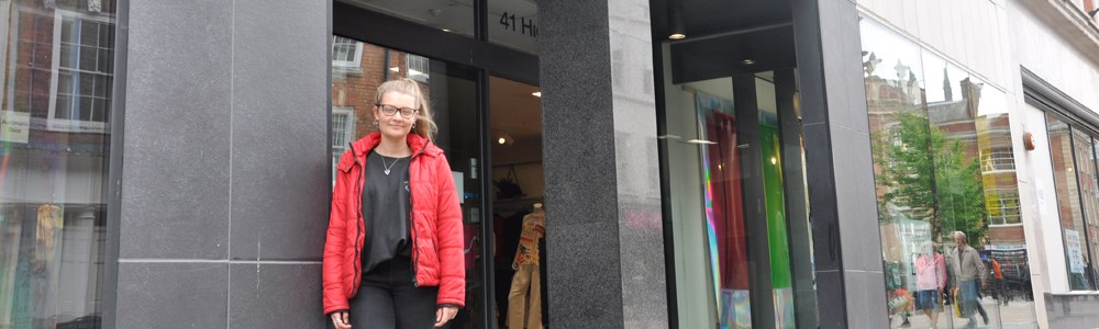 Female student stood in front of big grey fashion building
