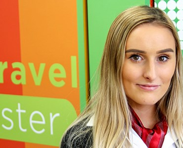 Female Travel and Tourism student stood in front of the Spires Travel Worcester logo