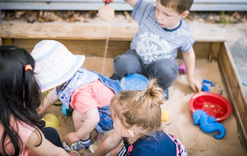 Four nursery children playing in sandpit at HoW College nursery