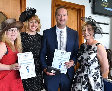 4 adults dressed smartly and smiling whilst holding travel agency awards