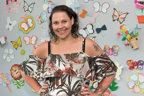 Female stood smiling with her hands on her hips in front of a grey wall with colourful paper butterflies and flowers on
