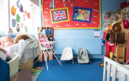 Picture of health and social care classroom; children's toys, clothes and bright colourful wall art.