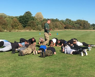 Group of male and female students holding the plank position in a large circle in the middle of a field, with a marine holding a stop watch in the middle.