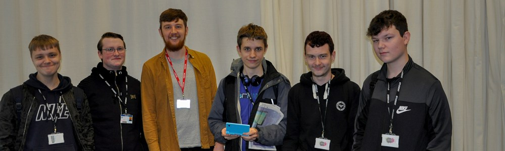 Group of male students stood smiling in front of large white drapes. Student in the middle holding a blue, handheld games device.