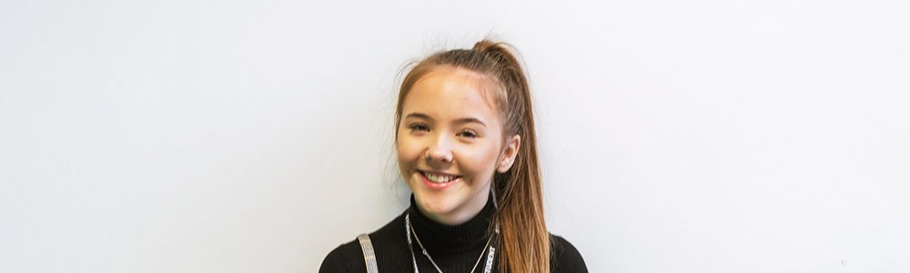 Female student with ponytail smiling in front of a white wall