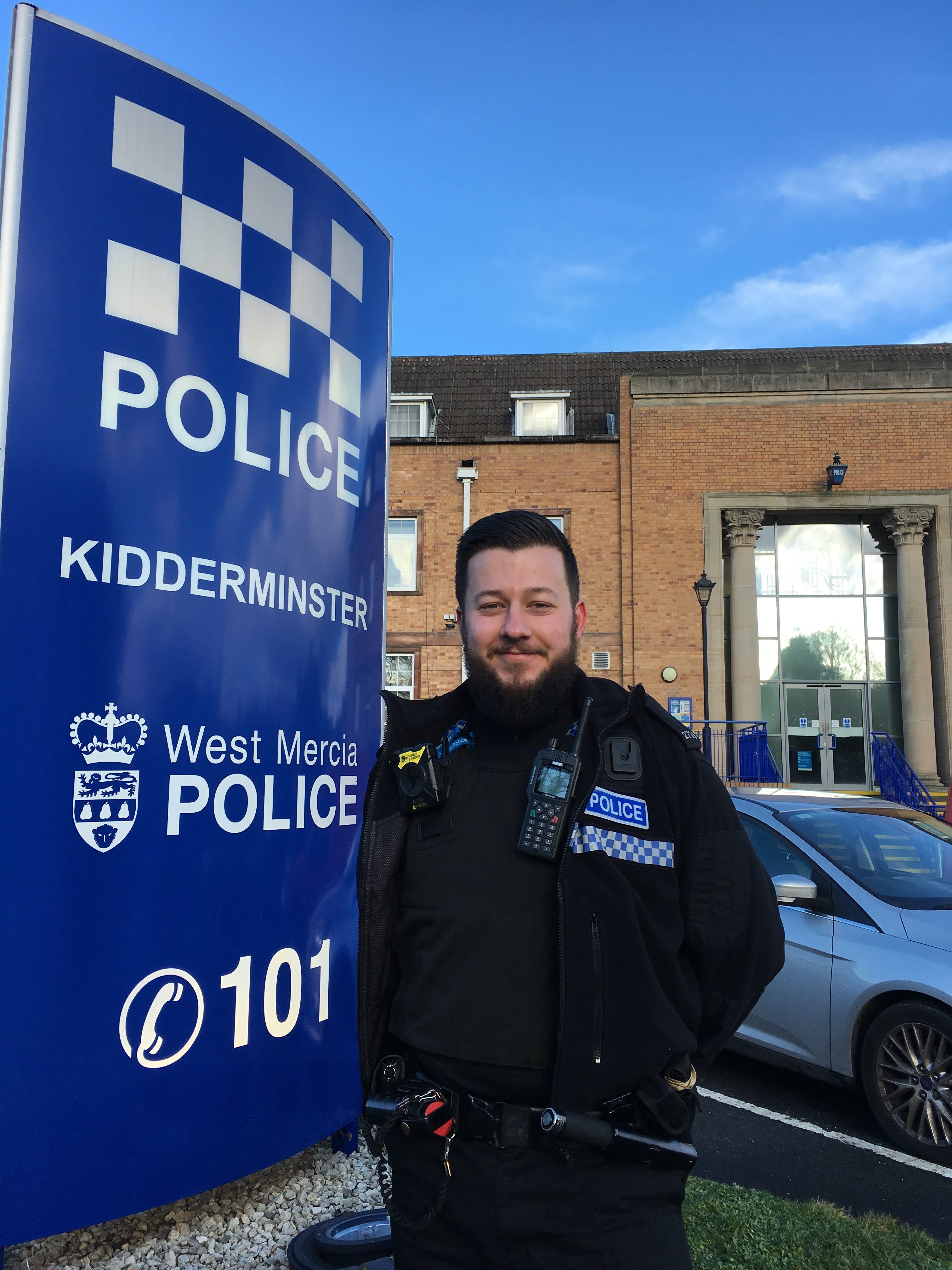 Male police officer with beard stood in uniform and smiling in front of the West Mercia Police Kidderminster sign