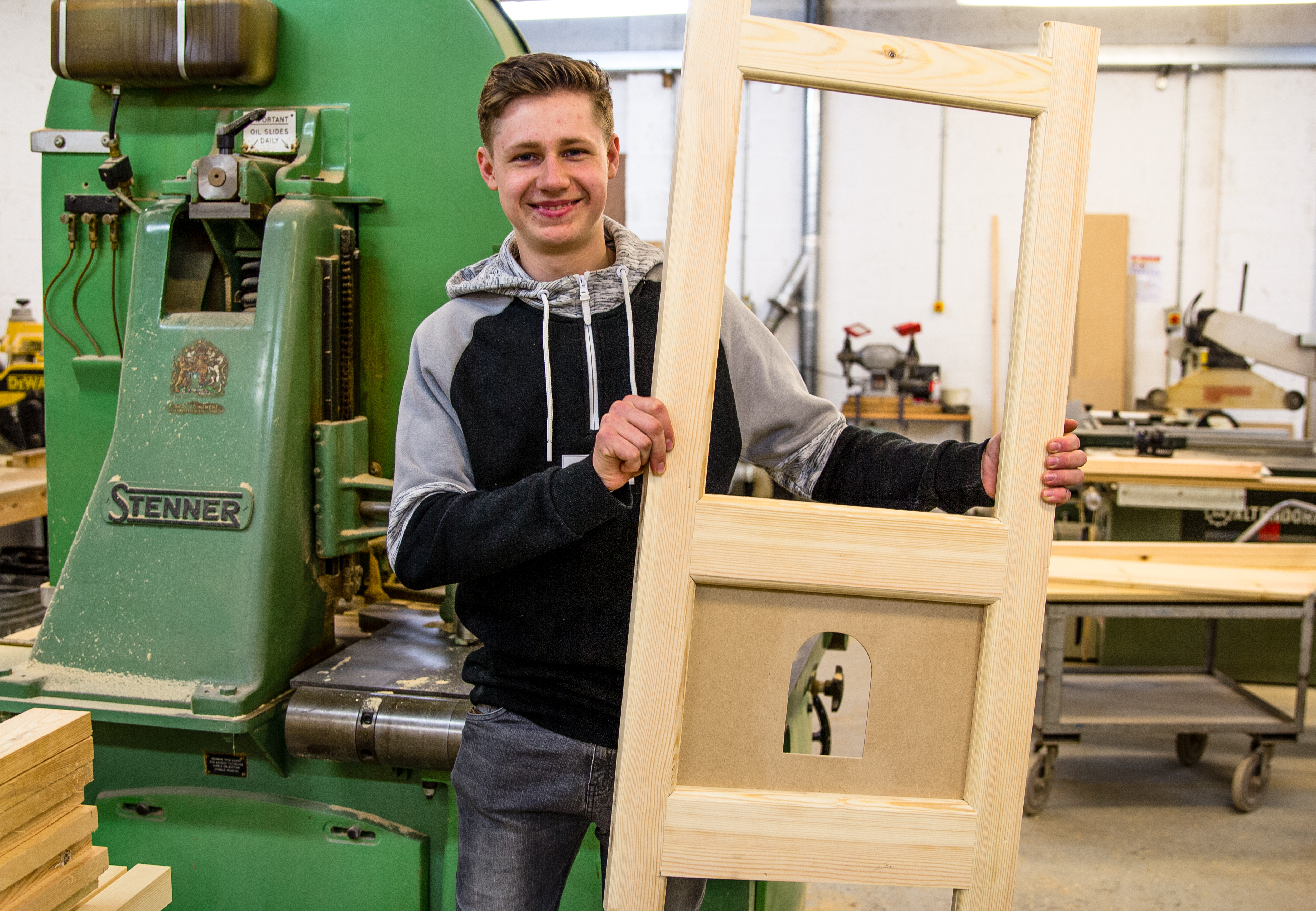 Smiling male student in front of green machine while holding a large, rectangular wooden item