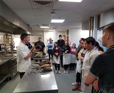 Male lecturer stood behind a stainless steel table in a commercial kitchen. Speaking to a class of students while holding a dead game bird.