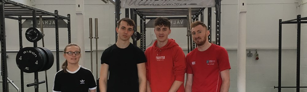 4 male and female students stood smiling on a black and wooden weightlifting platform in a gym.