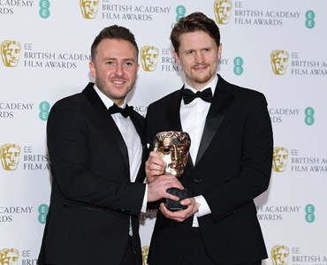 2 male adults in black tuxedos holding a Bafta award together while stood in front of a backdrop with Bafta logos on.