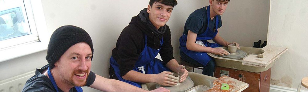 3 smiling male students in blue aprons molding clay pottery.