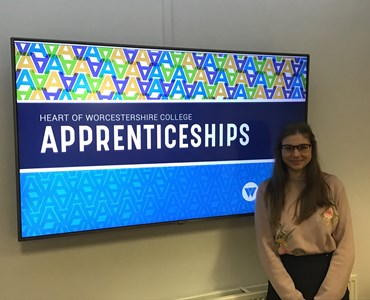 Female student stood in front of large TV with the Heart of Worcestershire College Apprenticeships logo on