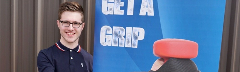 Male smiling in front of Get a Grip banner whilst holding a grip device in the palm of his hand