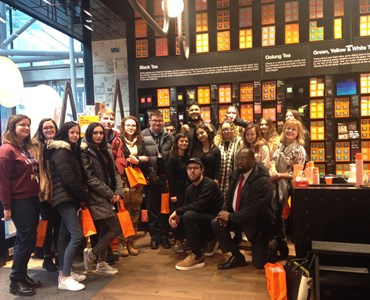 Large group photo of students smiling in T2Tea shop